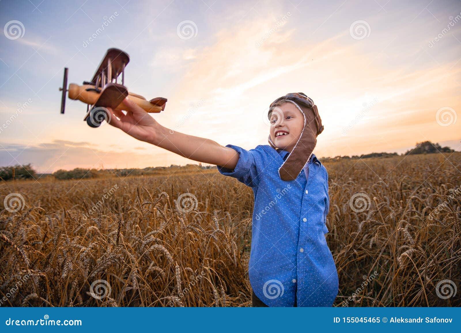 Un niño en un campo de trigo en el pueblo con un avión retro en sus manos Los sue?os del muchacho de hacer un piloto Igualaci?n d