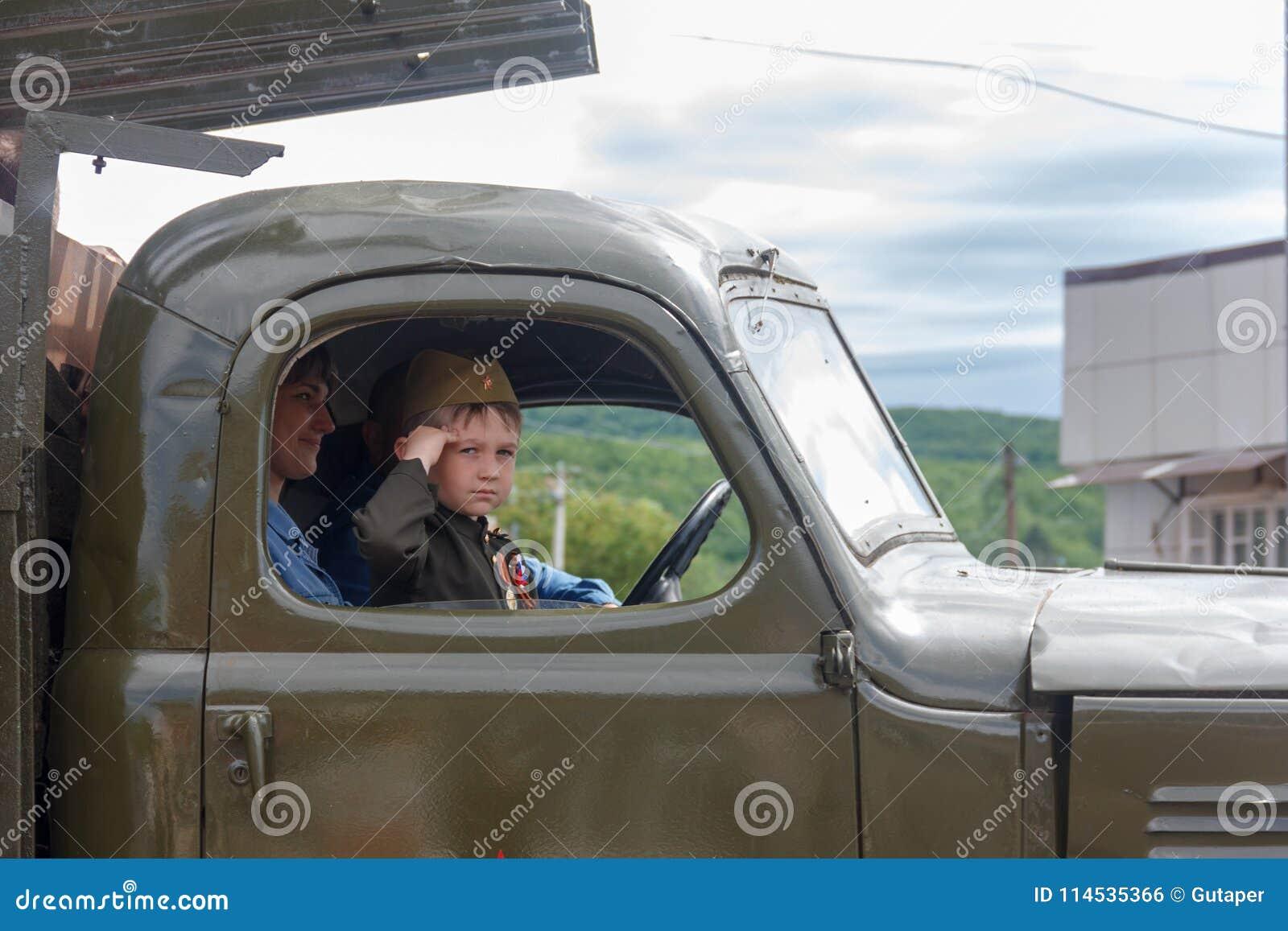 Un niño pequeño bajo la forma de soldado soviético en la carlinga de un coche del ejército participa en un desfile en honor de dí