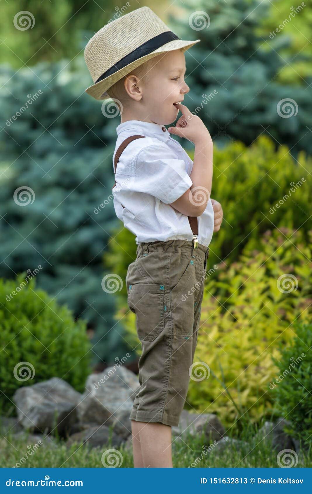 Un niño pequeño en un sombrero de paja camina en el parque Muchacho pequeño, tímido