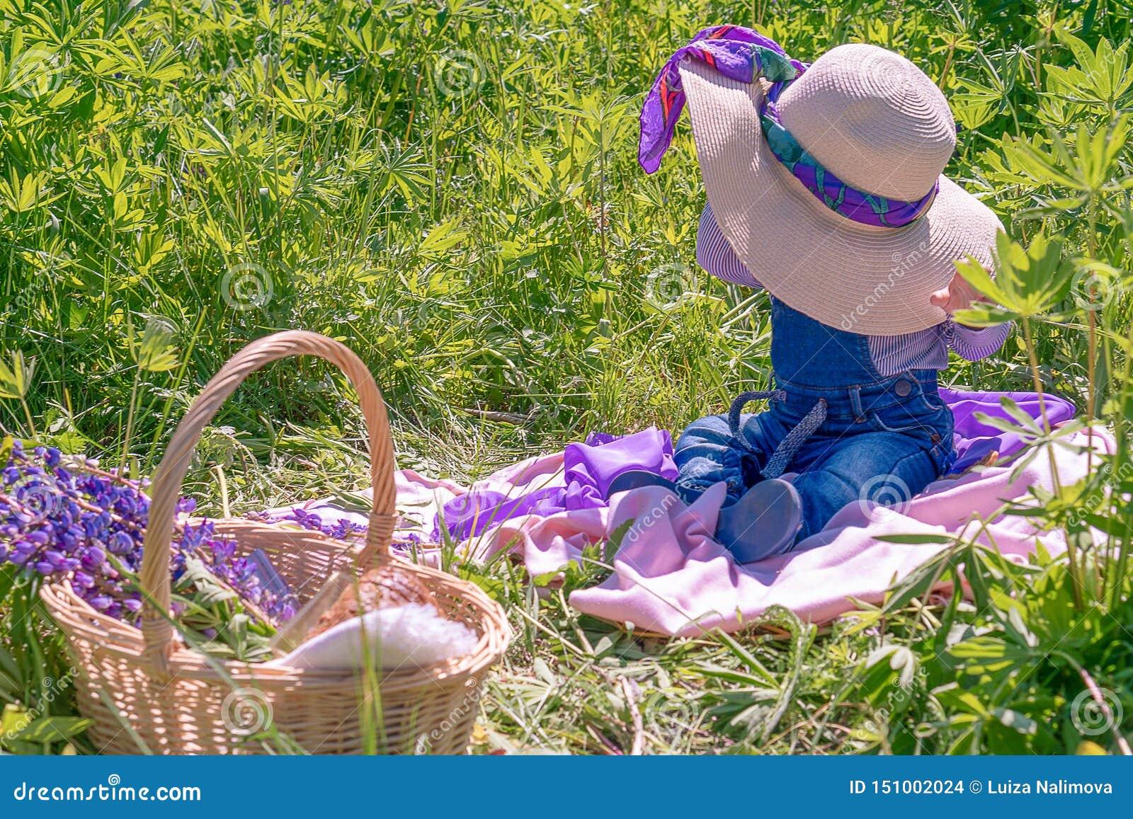 Un niño pequeño en un sombrero se sienta en un campo sorpresa El concepto de verano