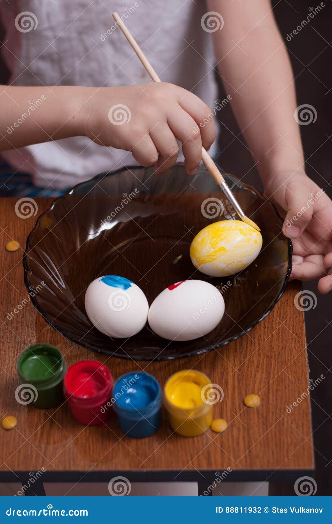 Un niño pequeño pinta los huevos la víspera de Pascua, de las pinturas coloridas y de cepillo,