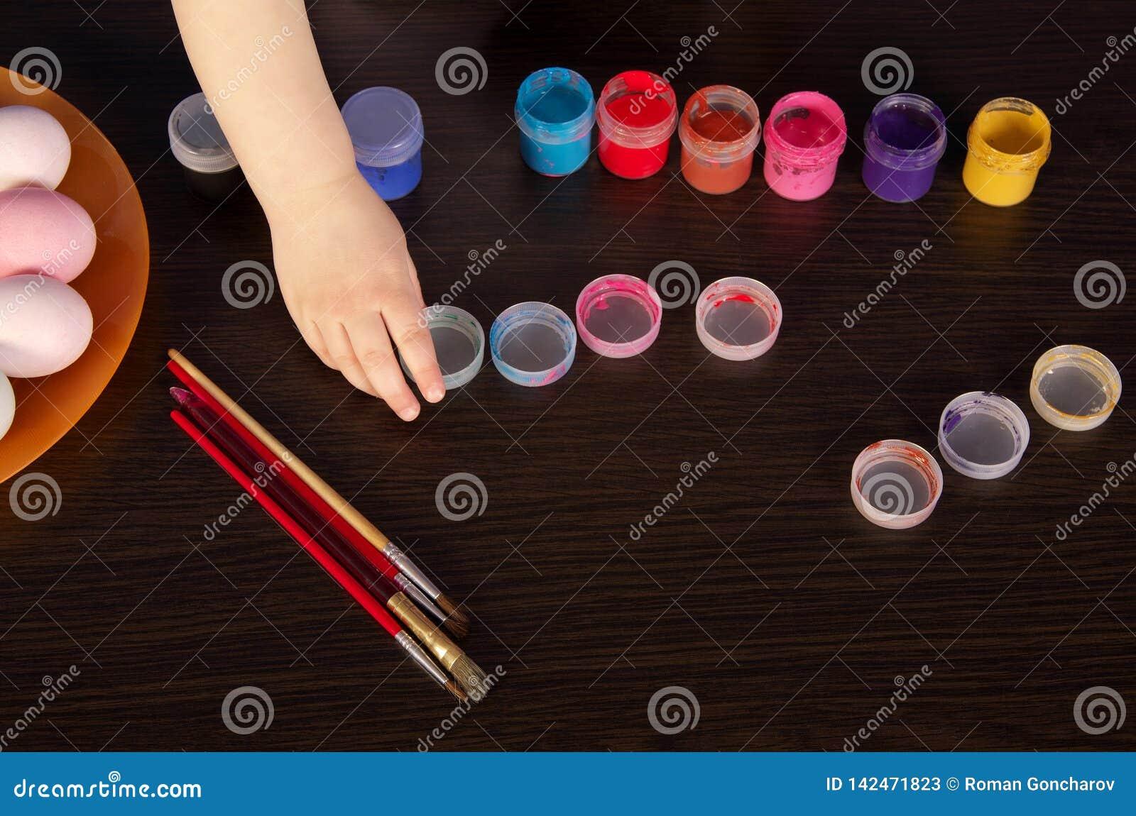 Un niño pinta los huevos de Pascua mano, brocha y pintura en la tabla Preparación para Pascua