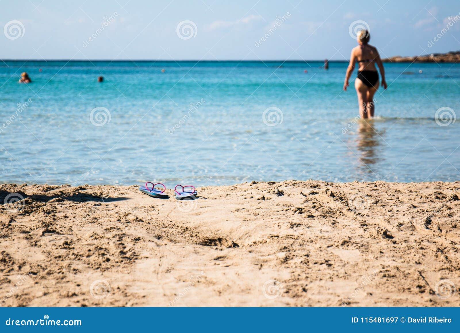 Un non identifié et hors de la femme de foyer entre dans l eau laissant ses sandales