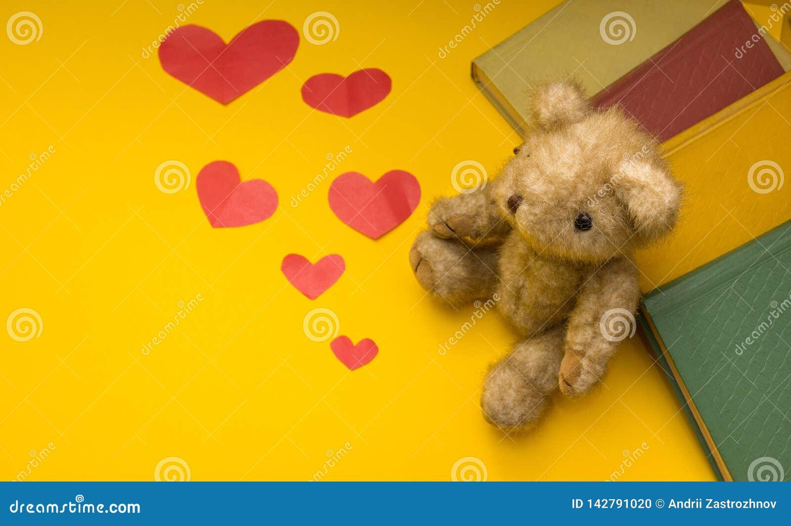 Un oso de peluche se sienta cerca de los libros en un fondo amarillo de corazones dispersados