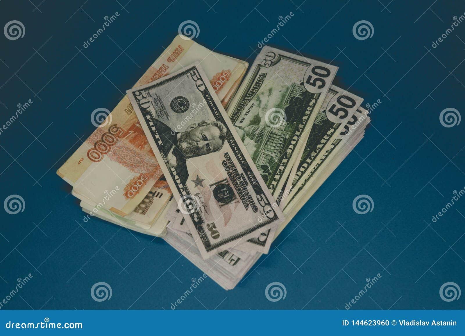 Un pacchetto delle rubli russe e dei dollari due batuffoli di soldi su un fondo blu ricchezza dell opportunit? Successo