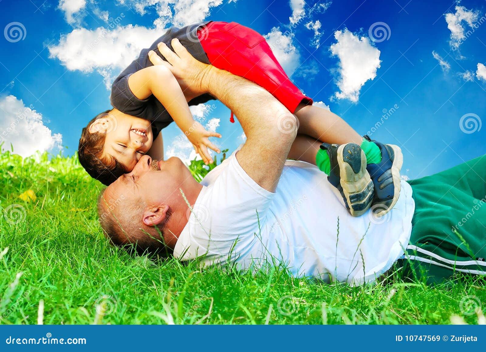 Un padre y un niño pequeño que ponen en hierba