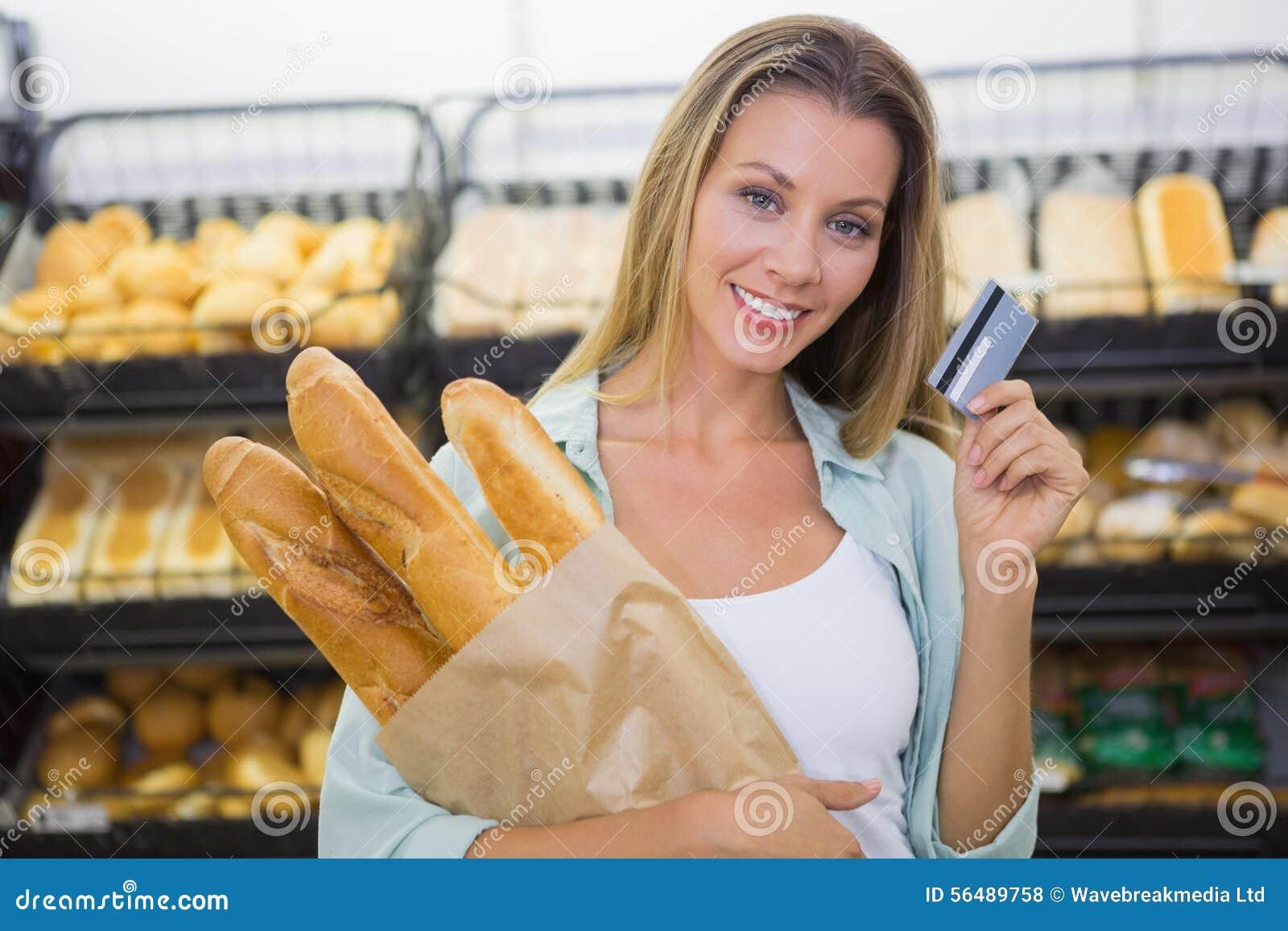 Un pain de achat de femme dans l étagère de pâtisseries