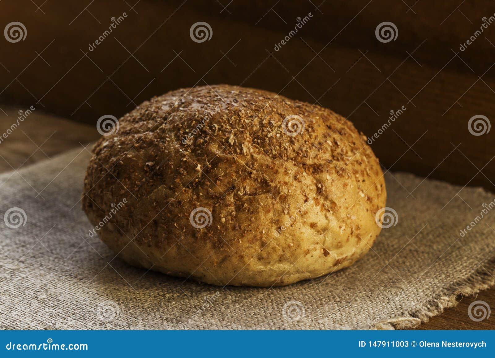 Un pain des mensonges de pain de seigle sur une serviette bleue naturelle de textile, le concept de la nourriture saine