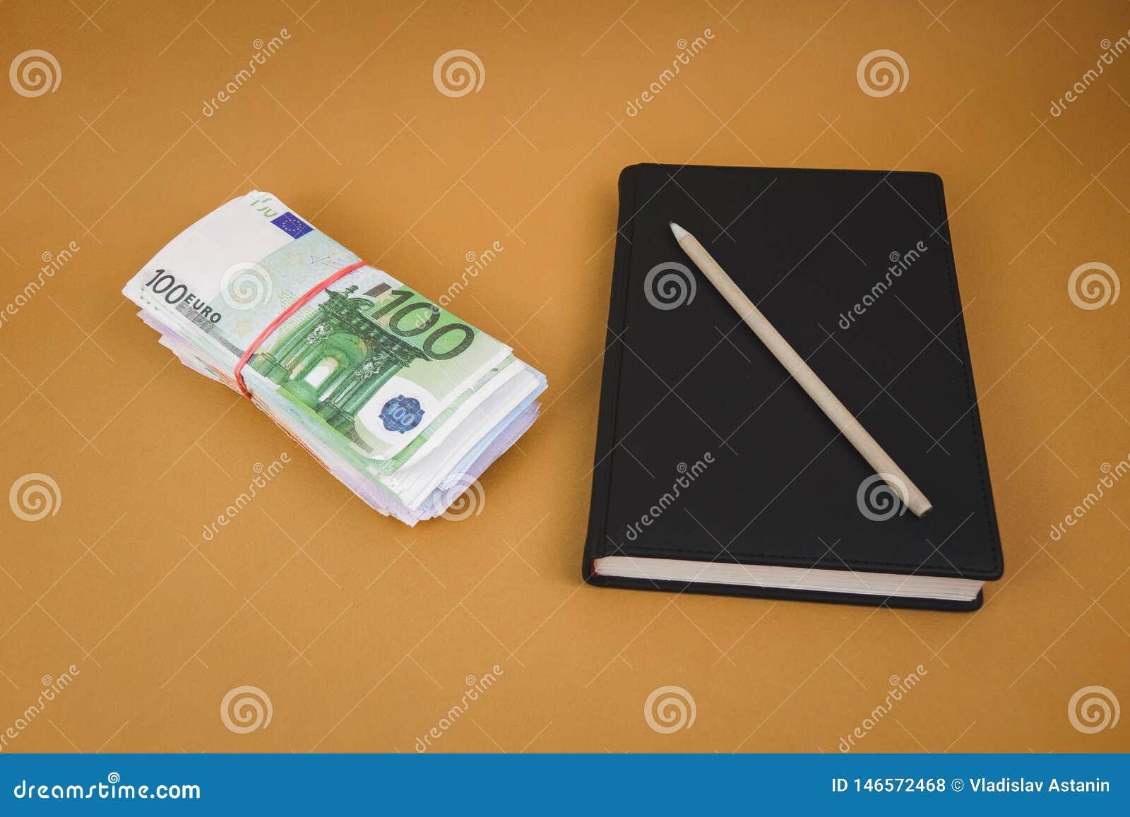 Un paquete de dinero un cuaderno negro en un fondo anaranjado llano