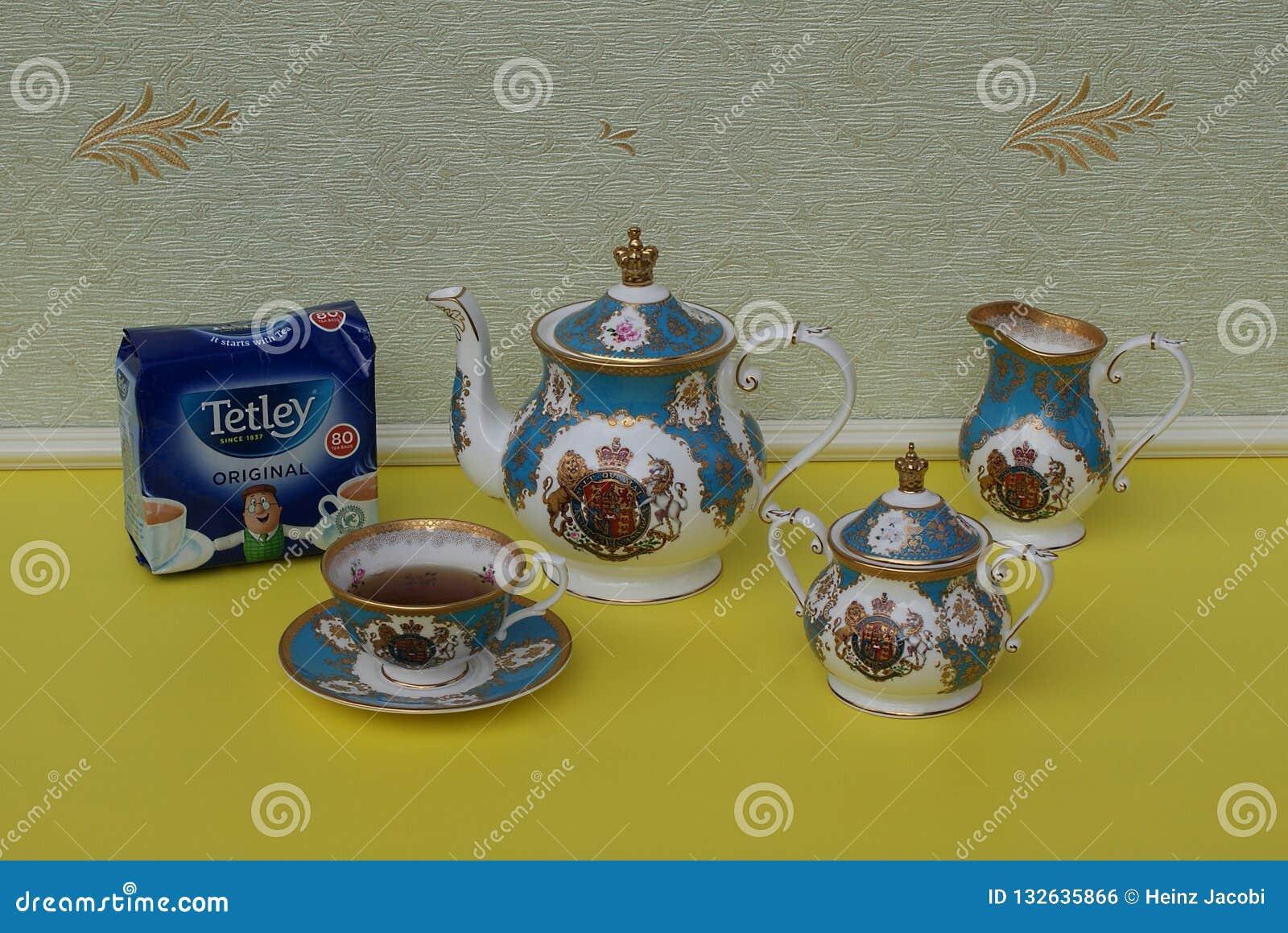 Un paquete de las bolsitas de té de Tetley inglés original siguientes una taza de té inglesa con el platillo, la tetera, el cuenc