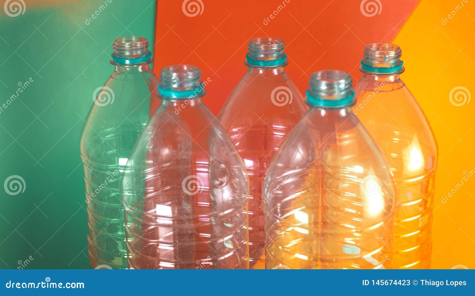 Un paquete de 5 vacíos y de botellas de agua reciclables, sin los casquillos, en un fondo vibrante coloreado con el verde de mar,