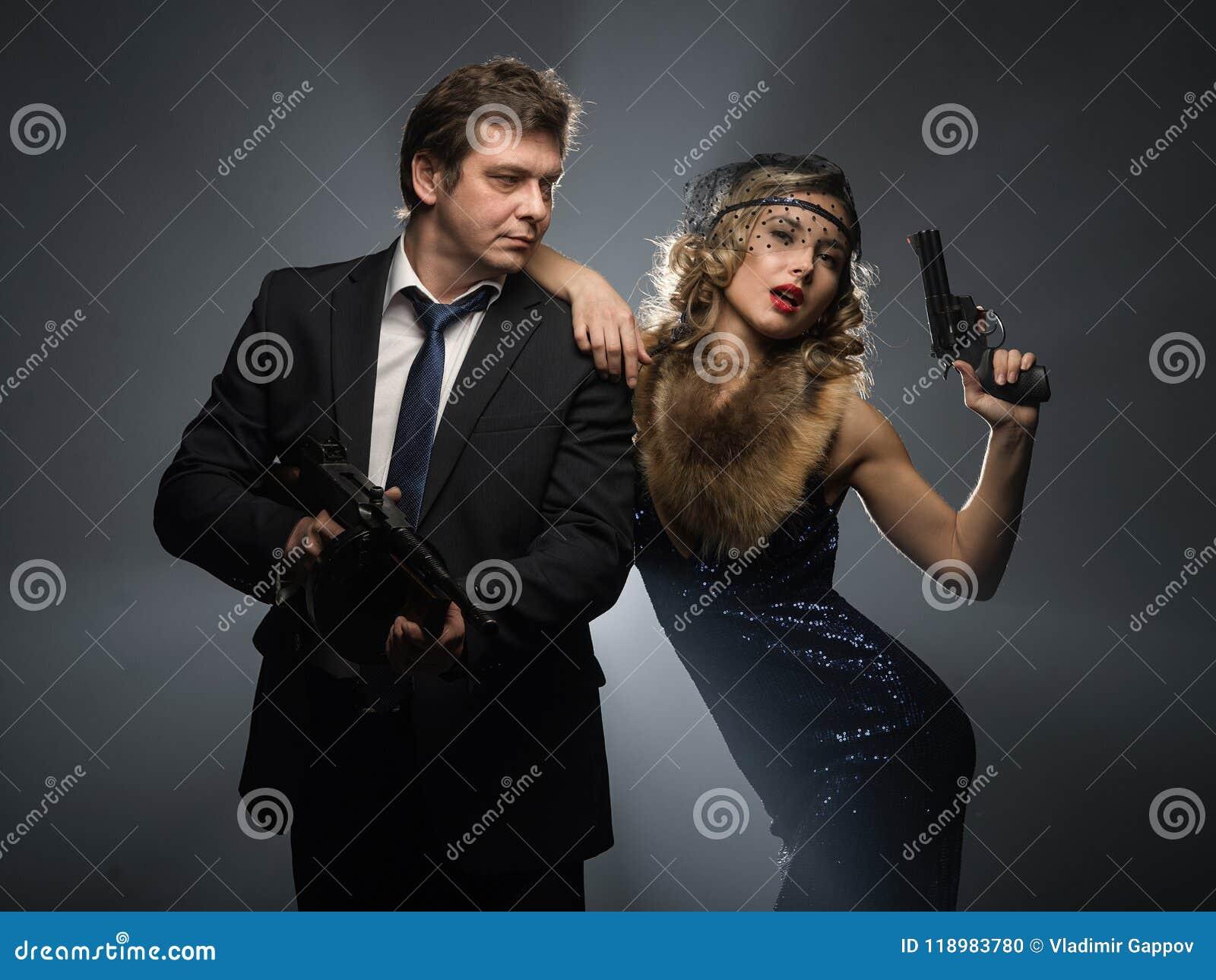 Un par de gángsteres, de un hombre y de mujer con los armas