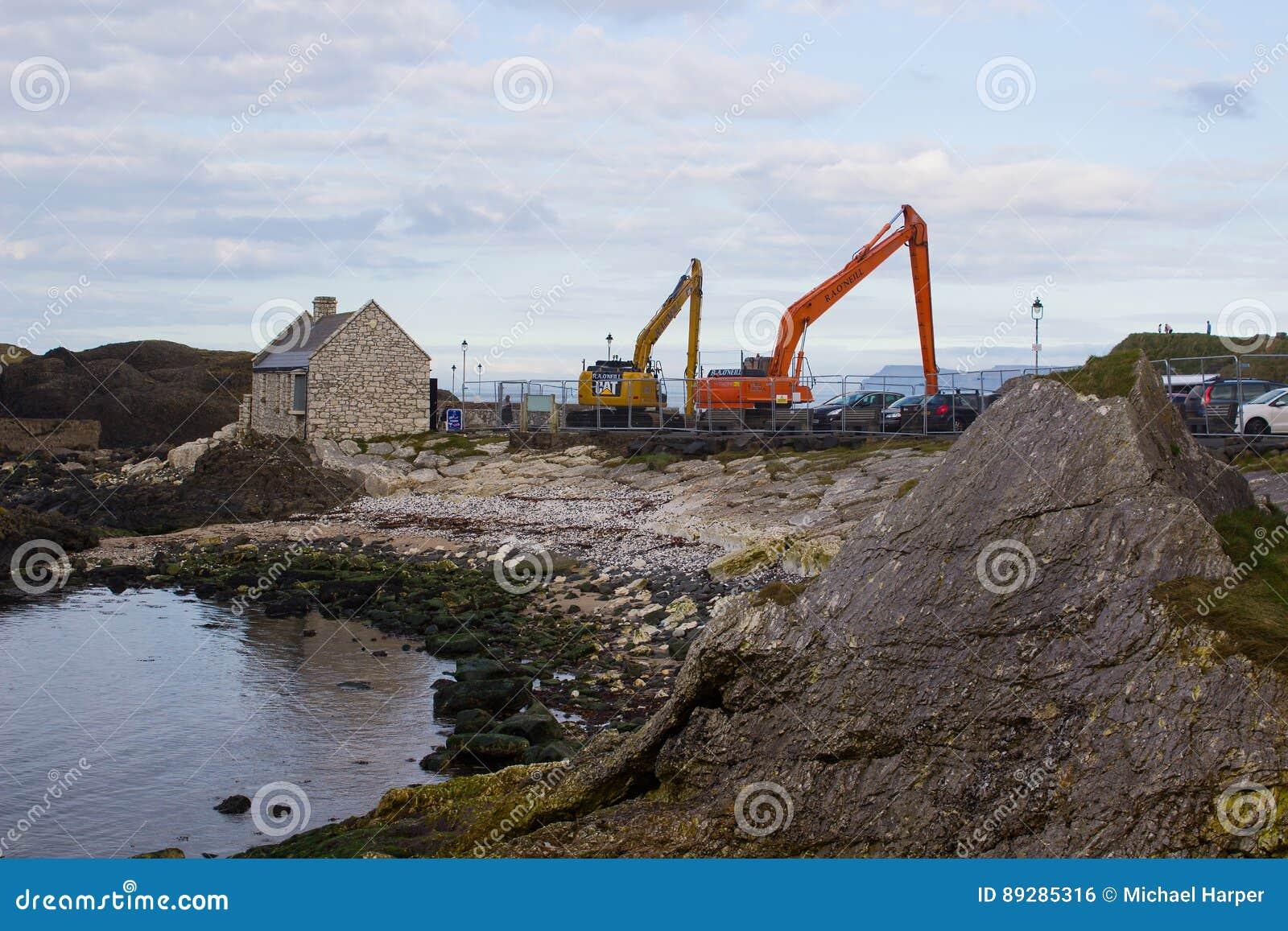 Un par de grúas usadas para dragar el pequeño puerto en Ballintoy en la costa del norte de Antrim de Irlanda del Norte en un día