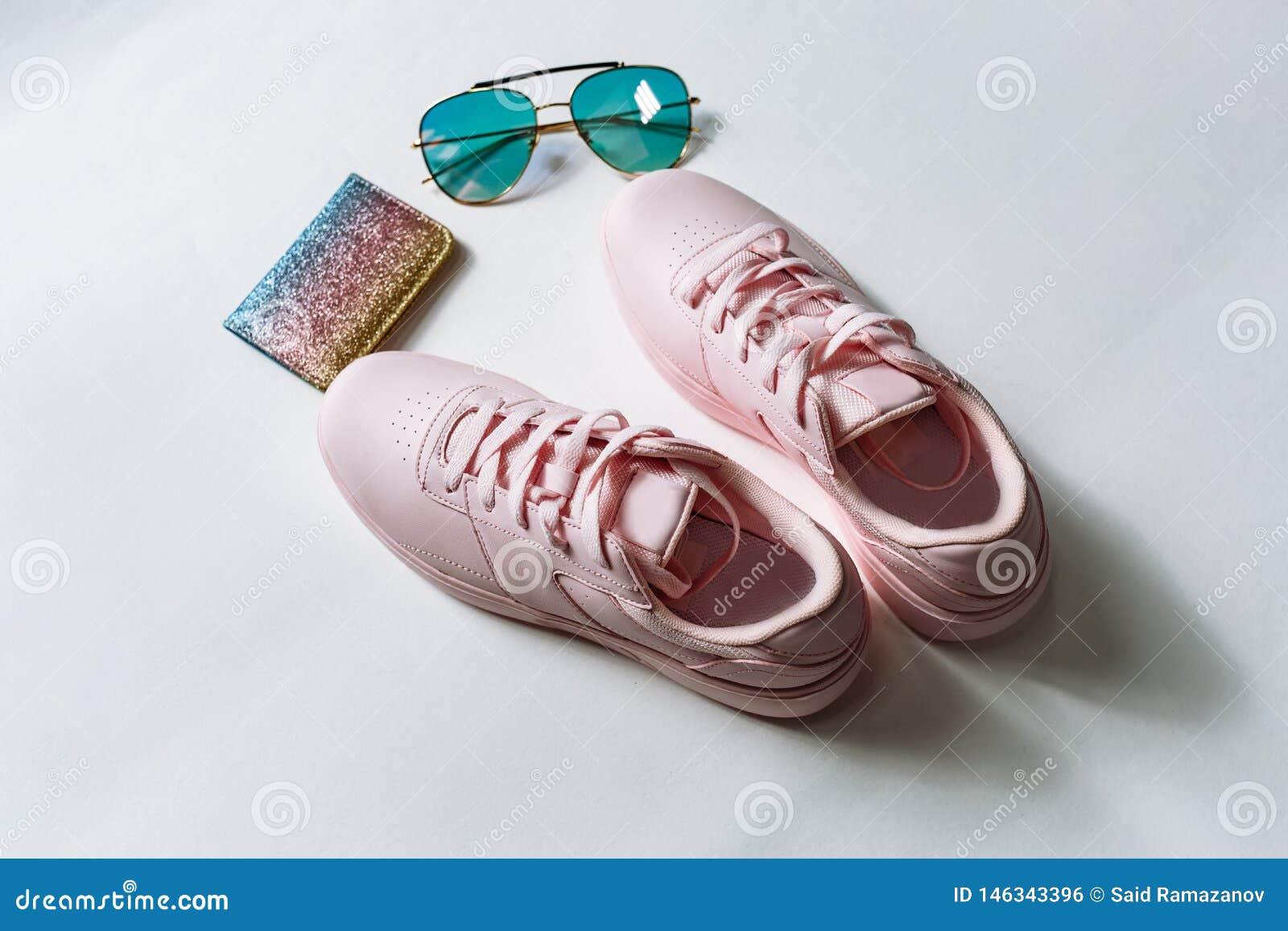 Un par de zapatillas de deporte de cuero rosadas, de un monedero con las lentejuelas multicoloras y de gafas de sol con el vidrio