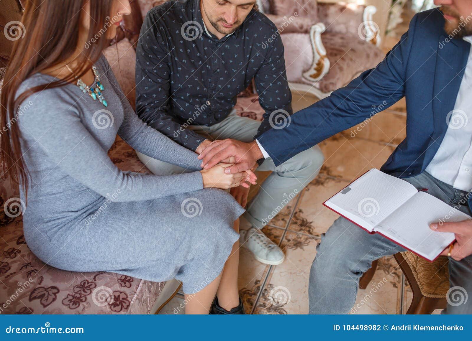 Un par en una recepción en un psicólogo lleva a cabo sus manos juntas y el doctor puso su mano en el top