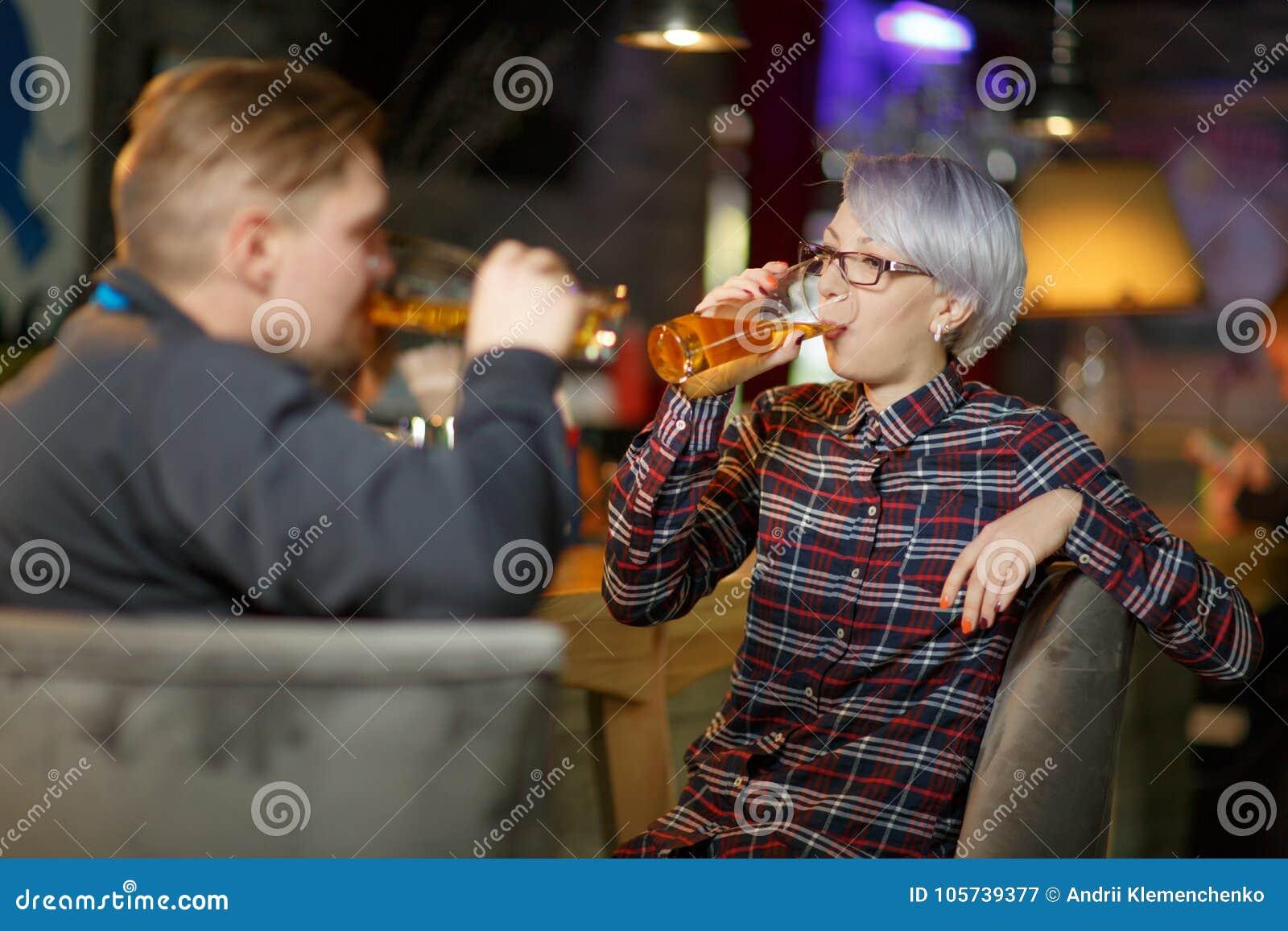 Un par está bebiendo la cerveza en una barra Dentro en un lugar público