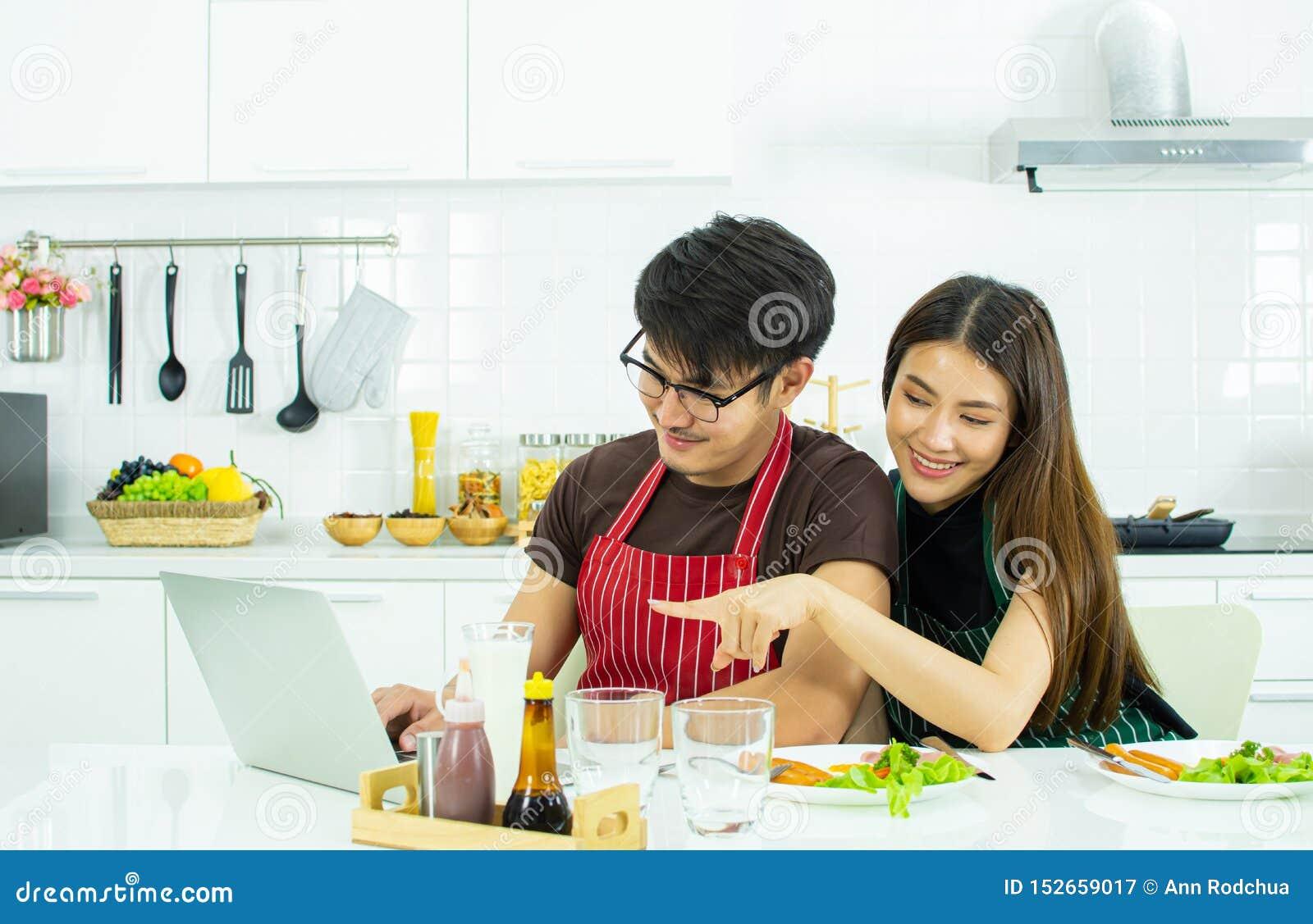Un par está utilizando el ordenador portátil mientras que desayunando en la cocina