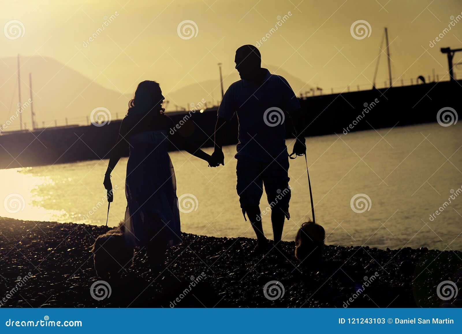 Un par feliz toma su perro para un paseo en la playa