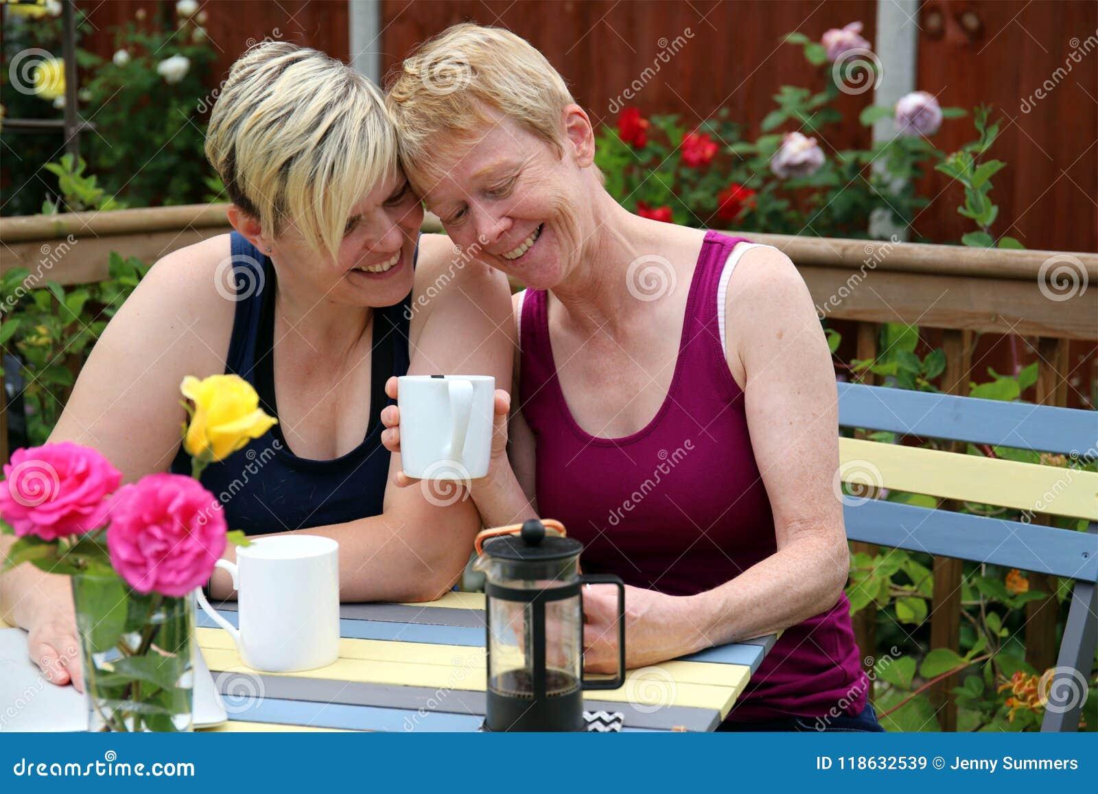 Un par gay feliz en casa en el jardín, y abarcamiento