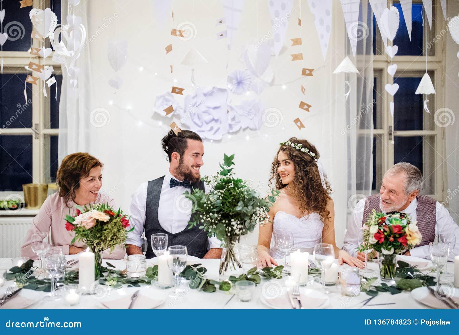Un par joven con los padres que se sientan en una tabla en una boda, mirando uno a