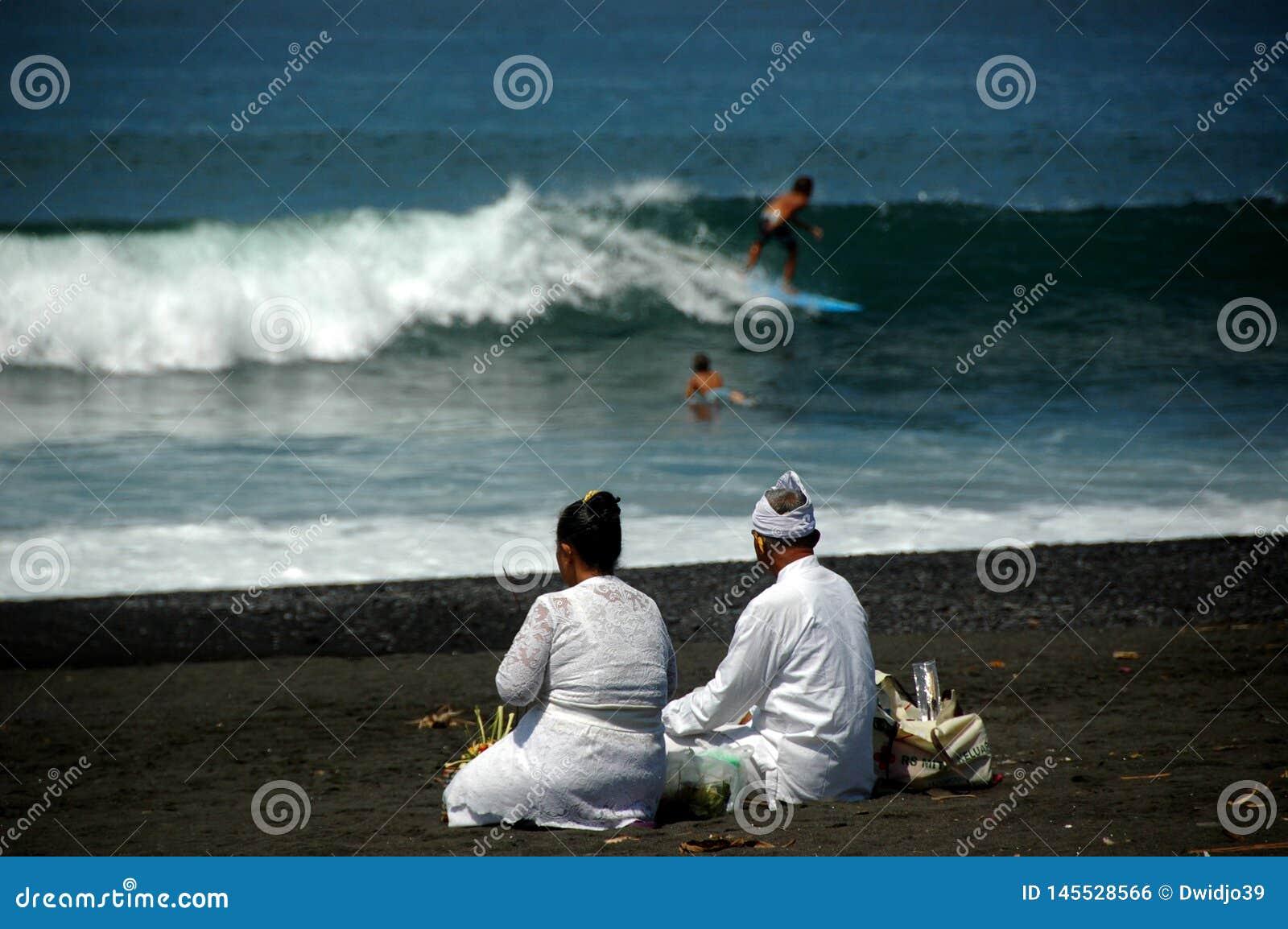 Un par mayor del Balinese que consigue listo para el ritual de la ma?ana en una playa