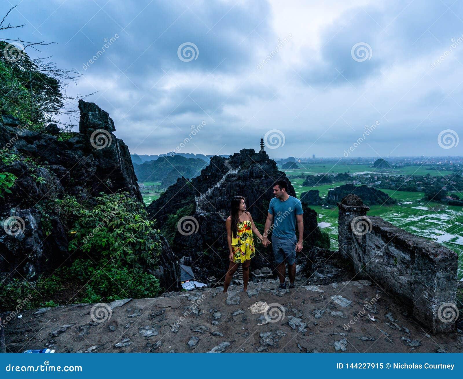 Un par pasa por alto las montañas de Vietnam septentrional de Hang Mua, un destino que camina popular