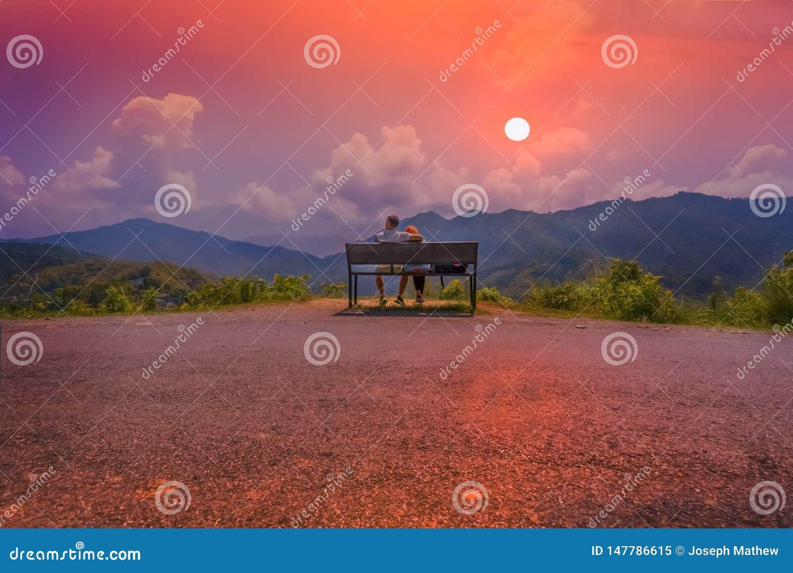 Un par que localiza en un banco que pasa por alto la puesta del sol asombrosa