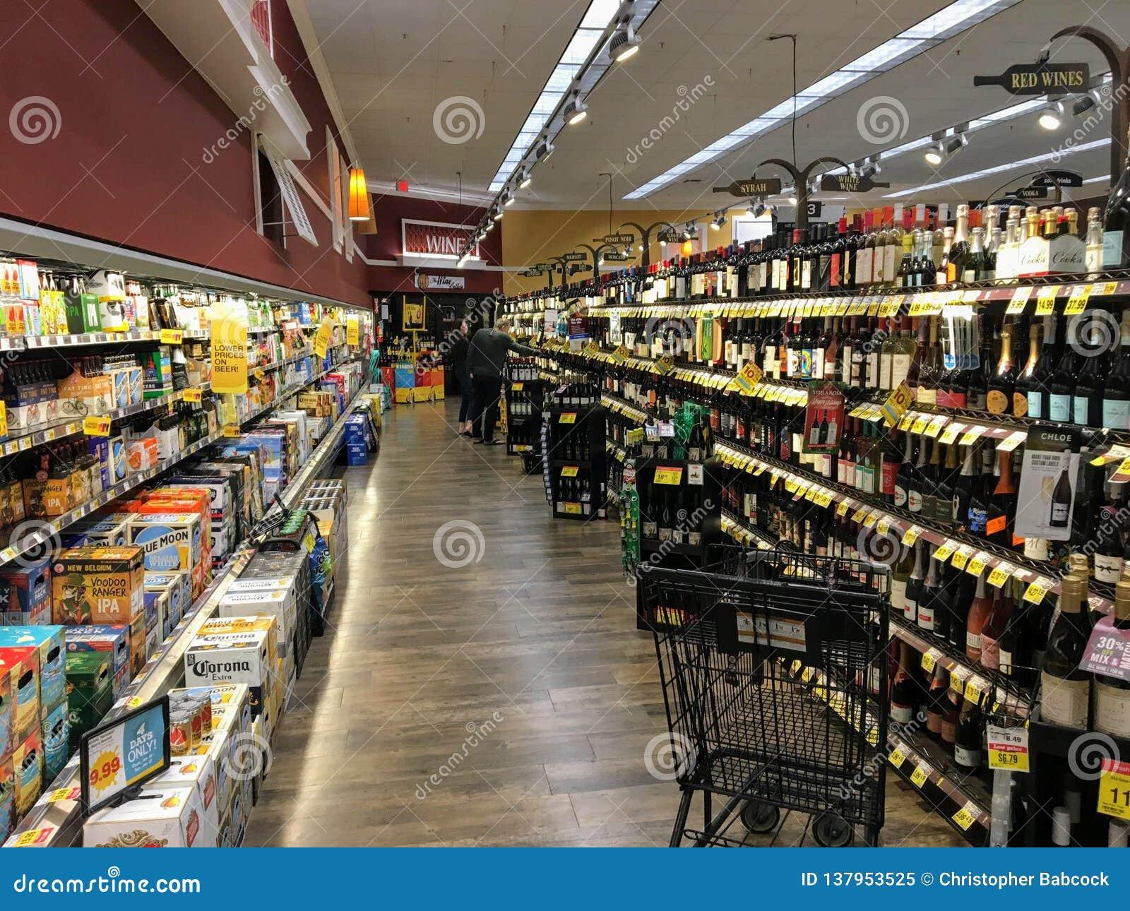 Un pasillo del colmado almacenado con opciones sin fin del vino y de la cerveza en Palm Desert, California, Estados Unidos