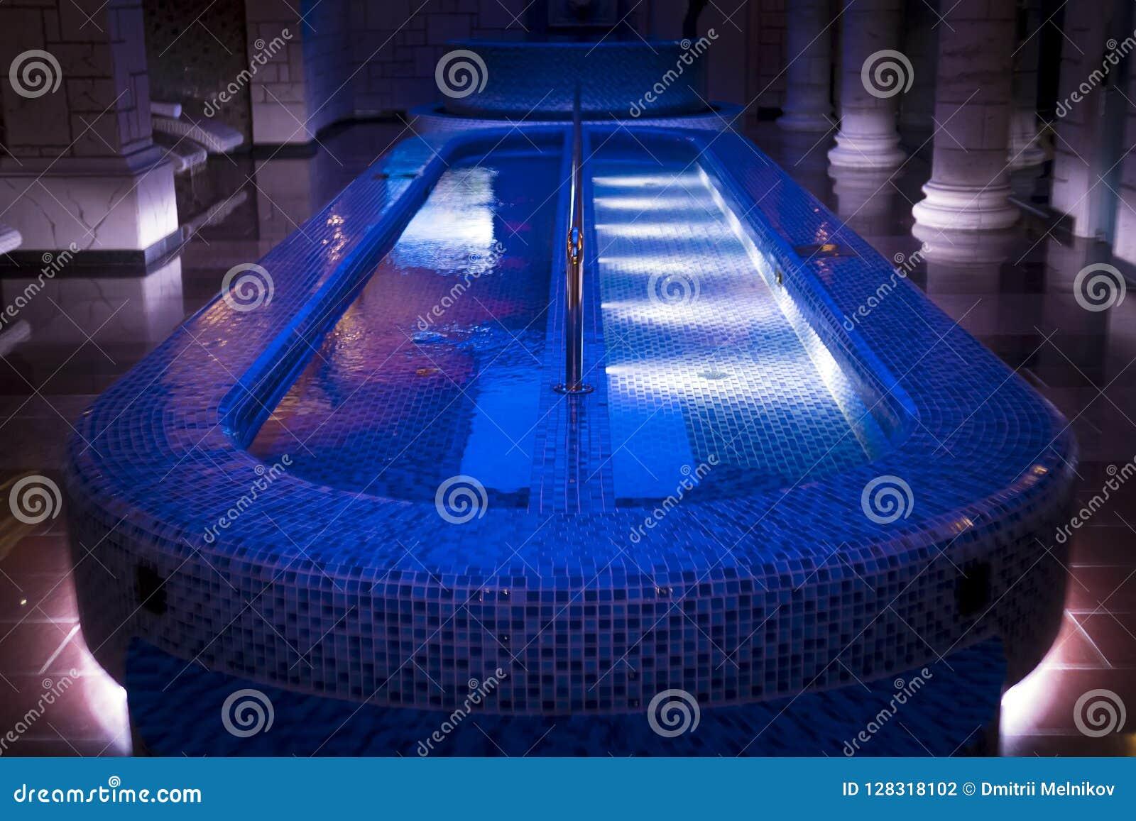Un pasillo sostenido con pilares de lujo del balneario con la piscina iluminada de la zambullida en el centro Una piscina azul-te