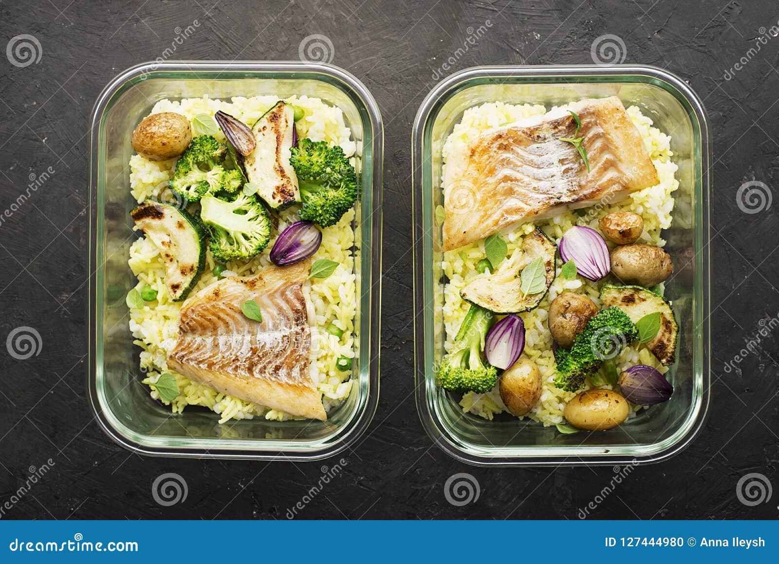 Un pasto sano per uno spuntino è una scatola di pranzo Contenitori di vetro con il pesce di mare fresco del vapore, riso con curc
