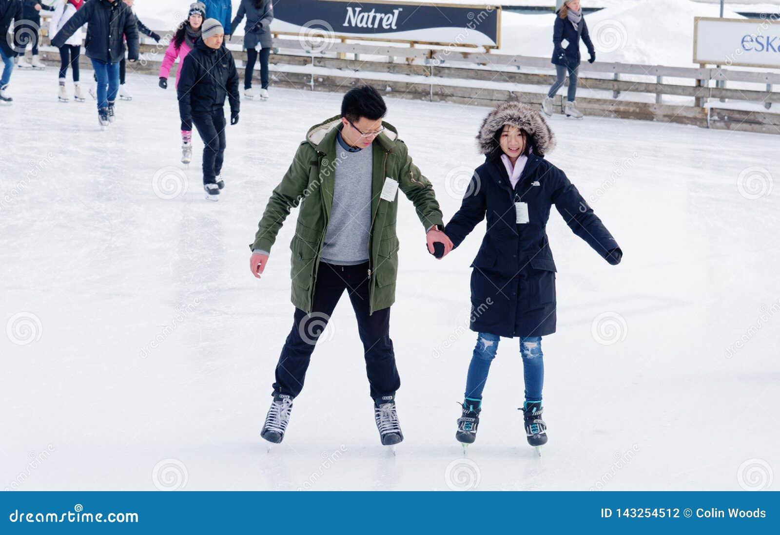 Un patinaje de hielo de los pares en una pista al aire libre en Montreal