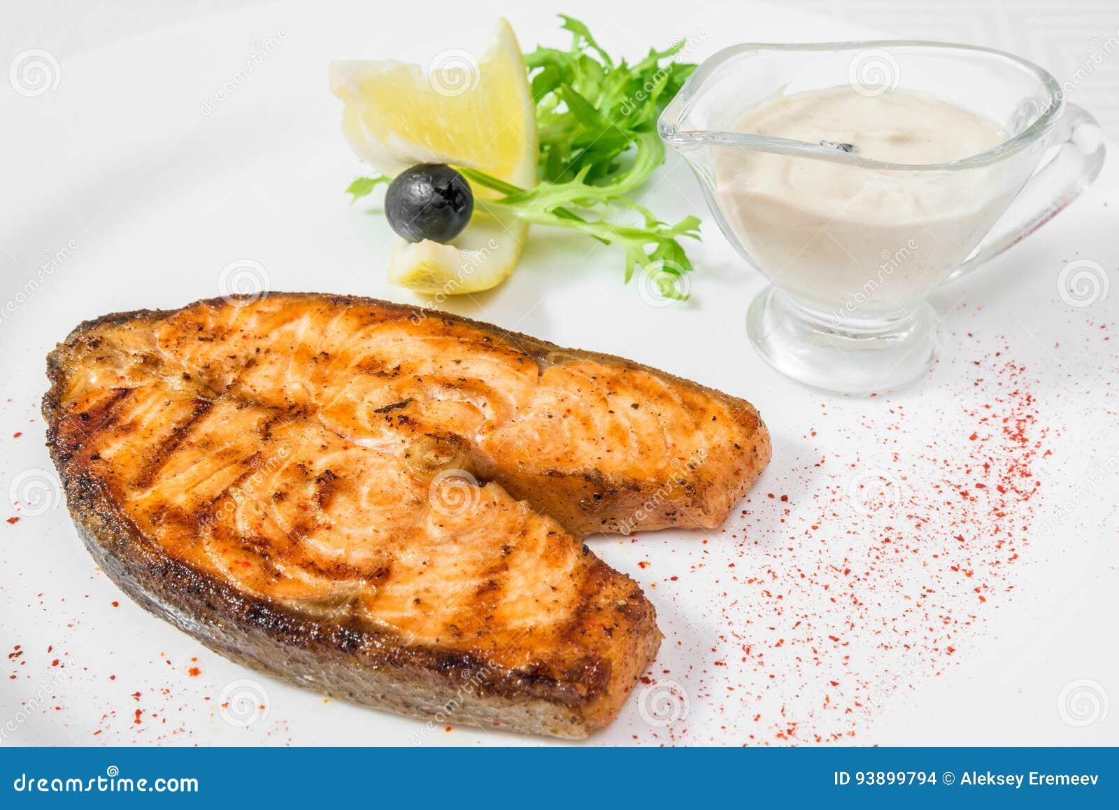 Un pedazo grande delicioso de pescados fritos con la salsa, el limón y las hierbas Marco horizontal