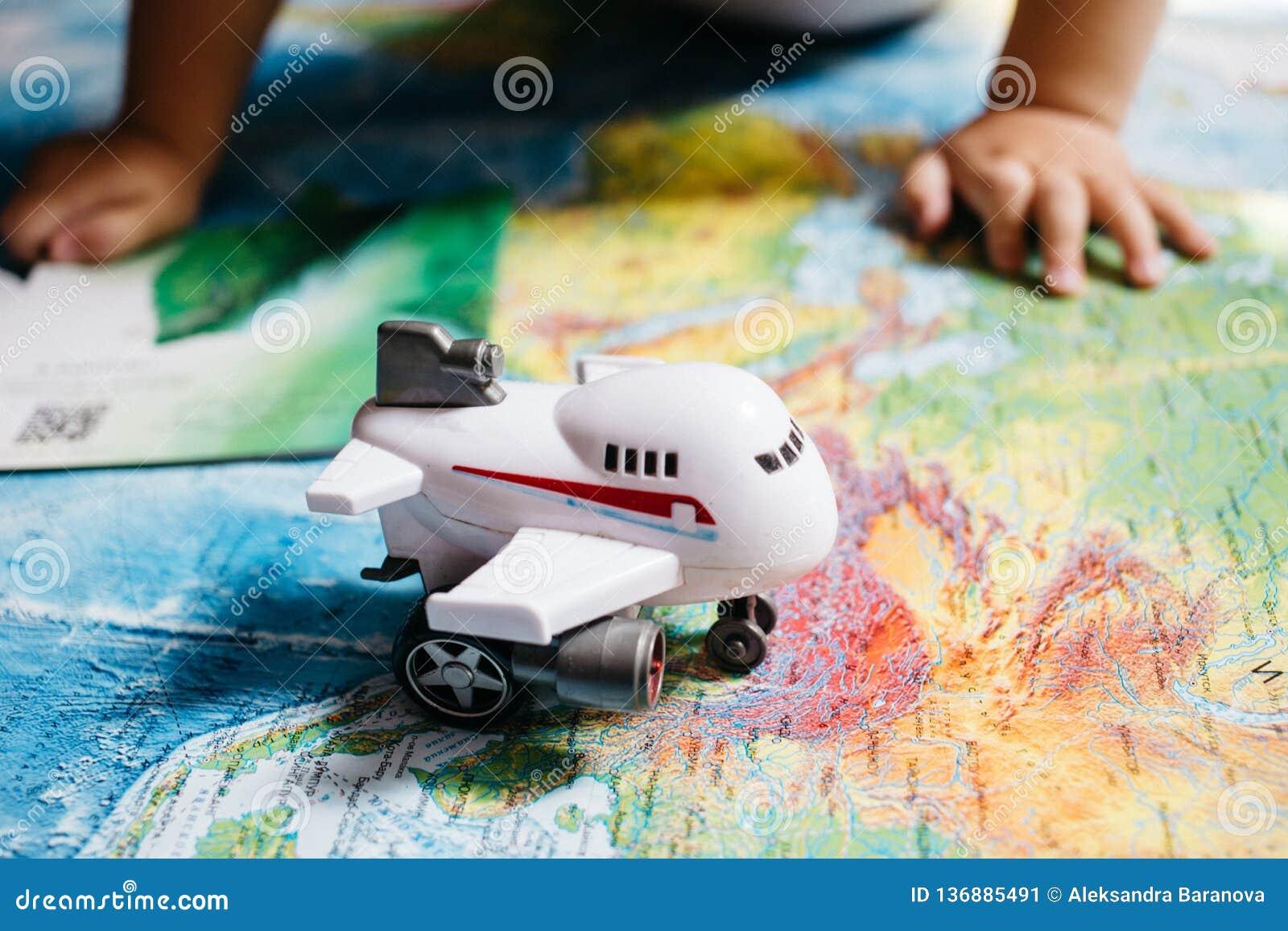 Un pequeño bebé que juega con un juguete de los aviones en el mapa del mundo, manos de los childs, viaje con los niños