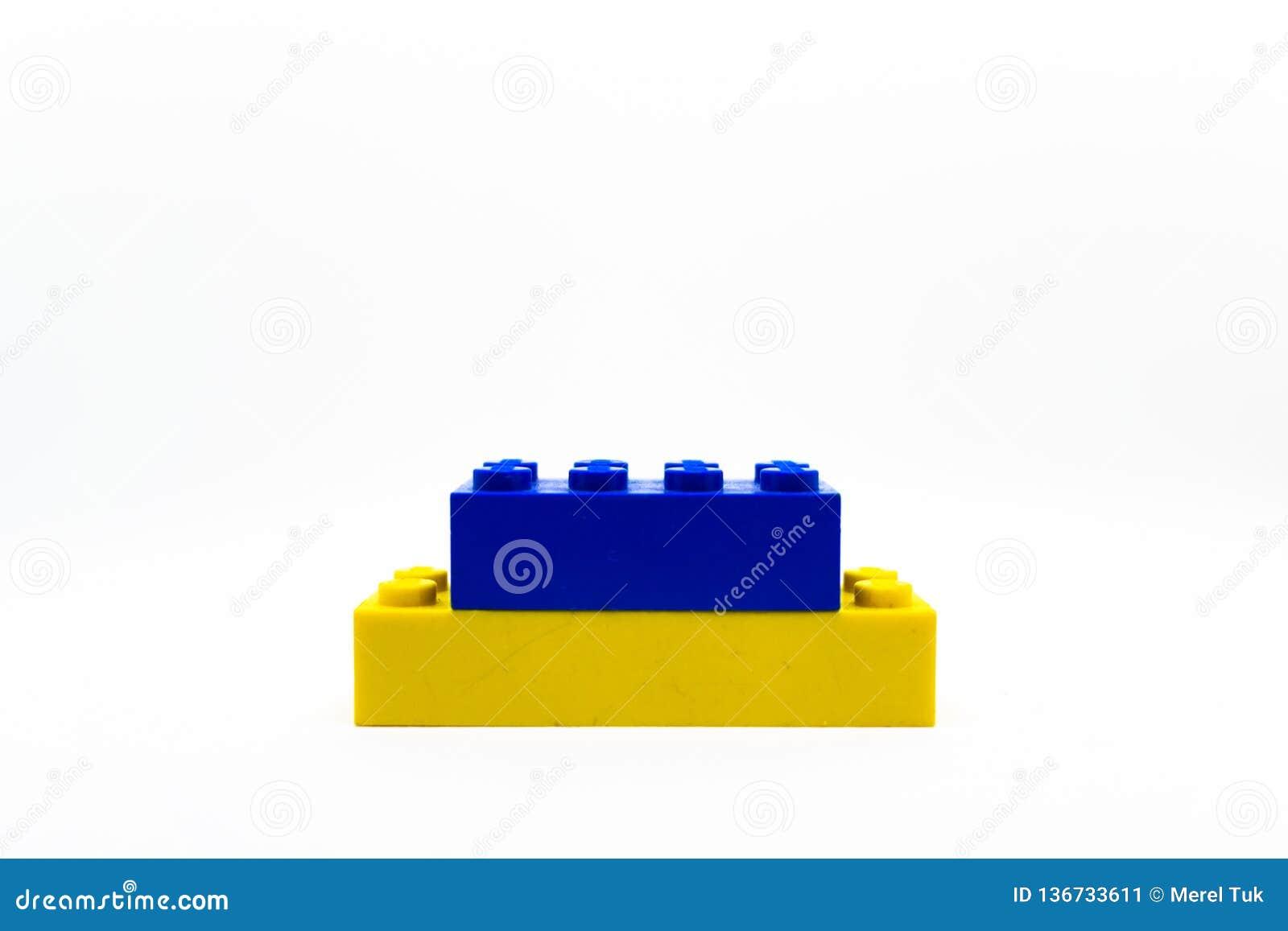 Un pequeño bloque azul y amarillo de Lego aislado en el fondo blanco