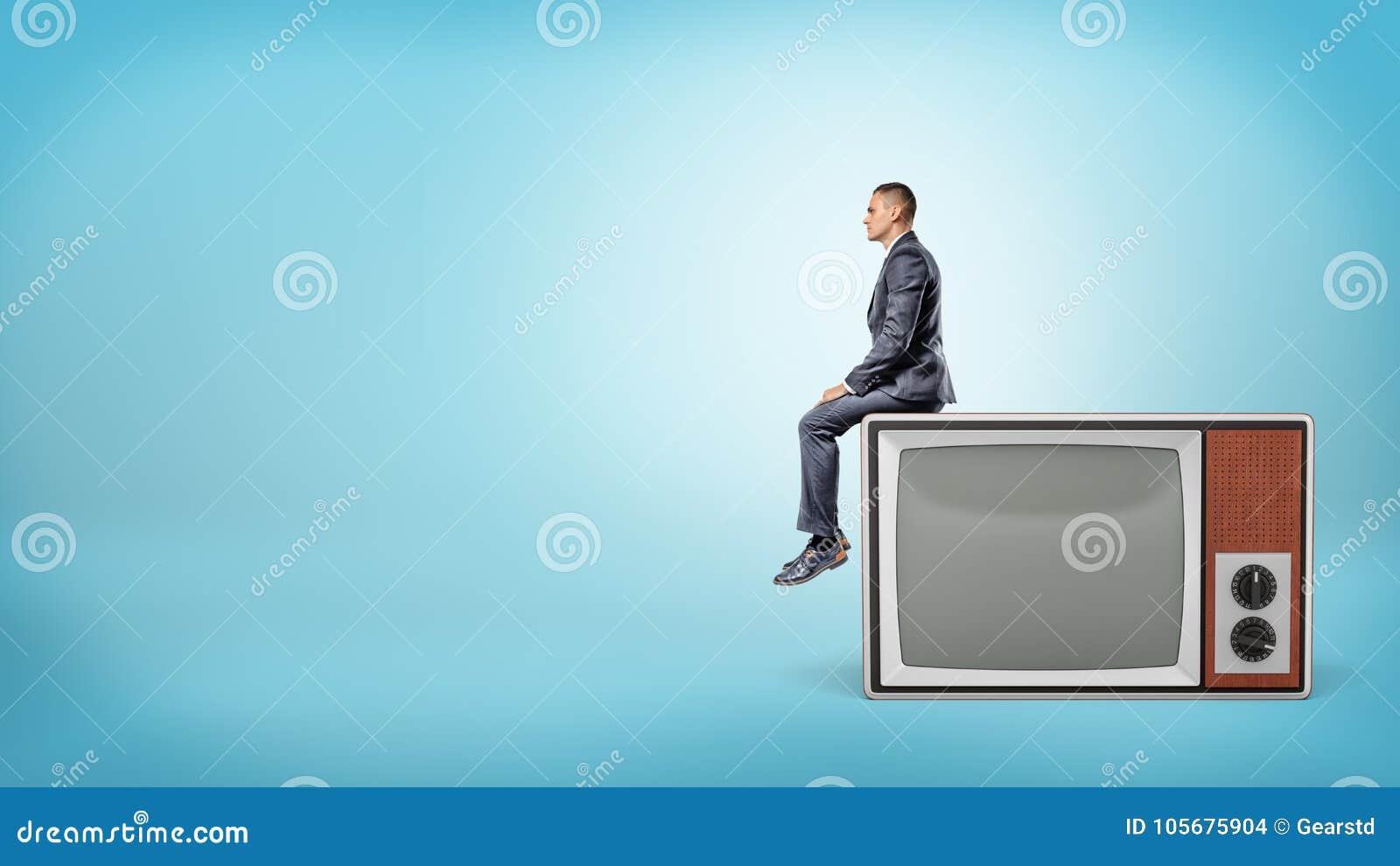 Un pequeño hombre de negocios se sienta en vista lateral en un aparato de TV retro gigante con la pantalla en blanco