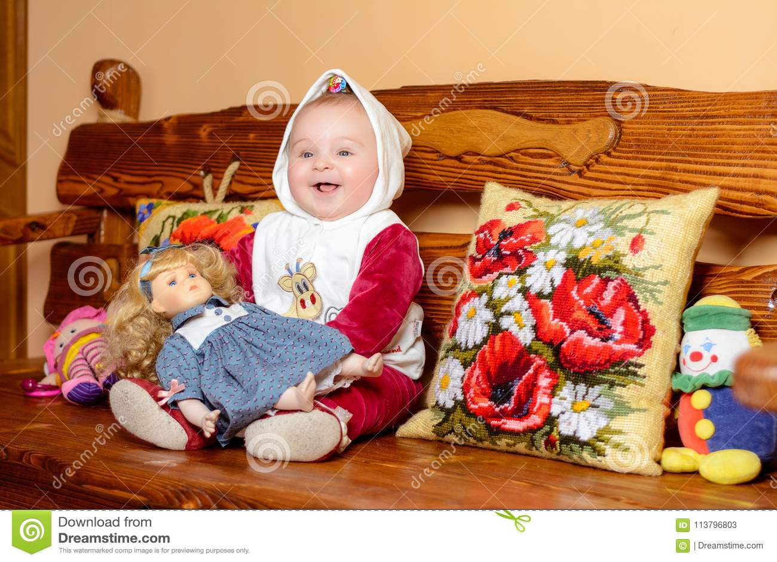 Un pequeño niño en un mantón que se sienta en un sofá con las almohadas bordadas