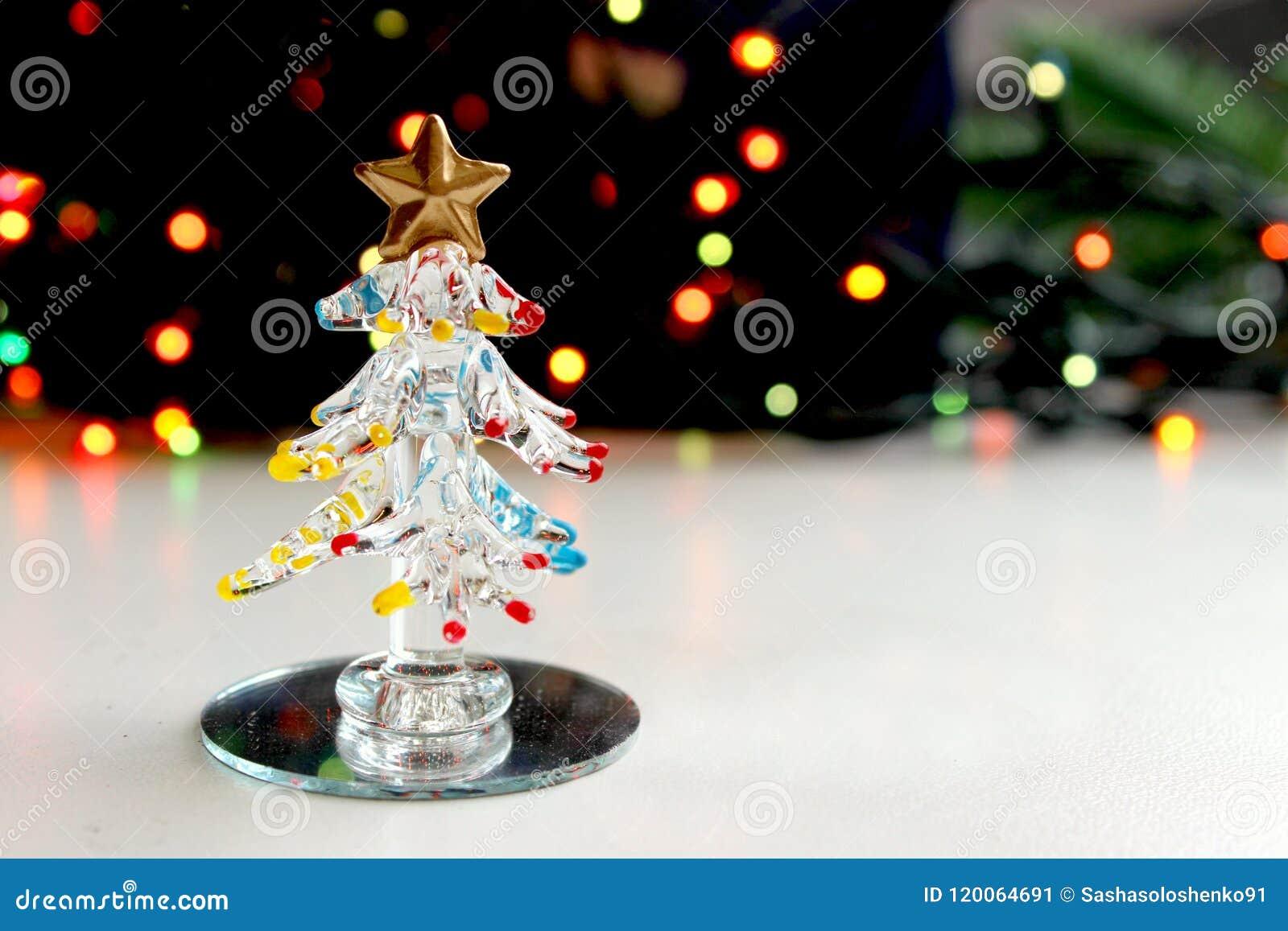 Un petit arbre de Noël de souvenir fait de verre sur le fond des lumières de Noël de scintillement, effet de bokeh