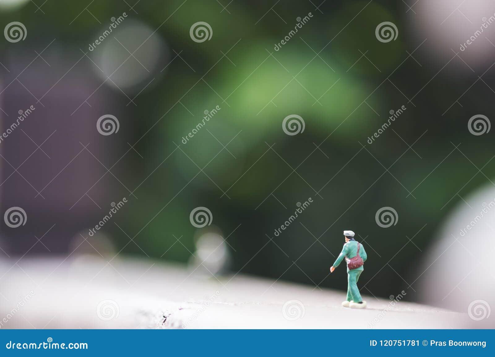 Un petit chiffre de modèle de soldat sur le plancher en bois avec le fond de nature de vert de tache floue