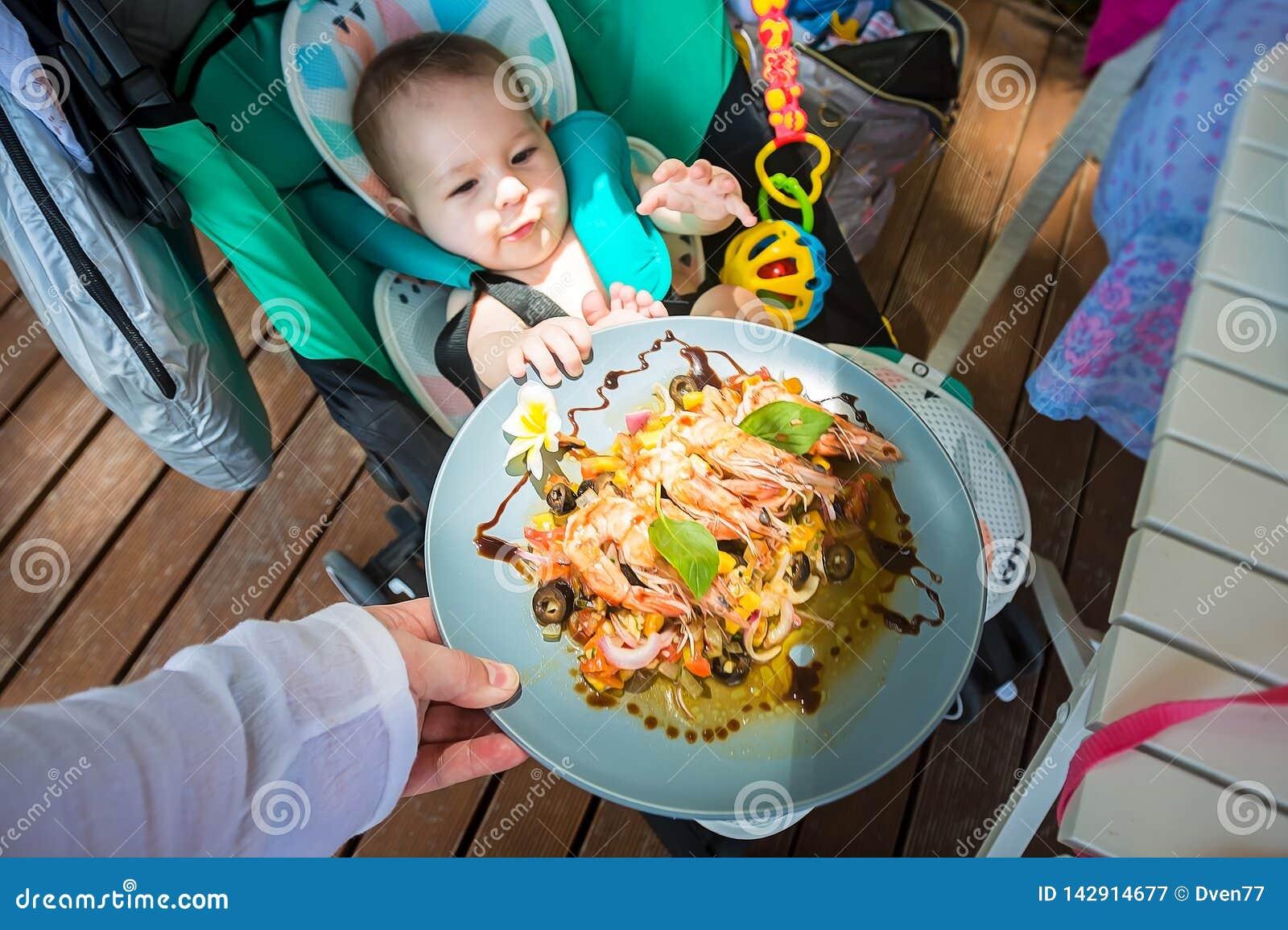 Un petit enfant à 8 mois veut manger de la nourriture adulte et tire un plat des crevettes et des légumes à lui Bébé s asseyant d