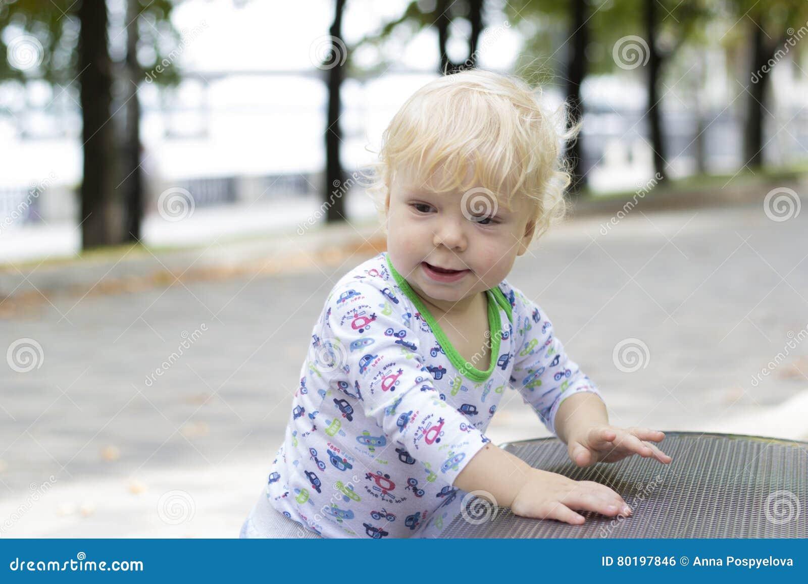Un petit enfant apprend à marcher près des bancs, enfant en bas âge