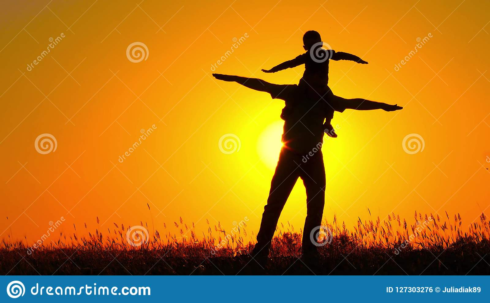 Un petit enfant tournant sur son ` s de père épaule Famille heureuse jouant au coucher du soleil Silhouette