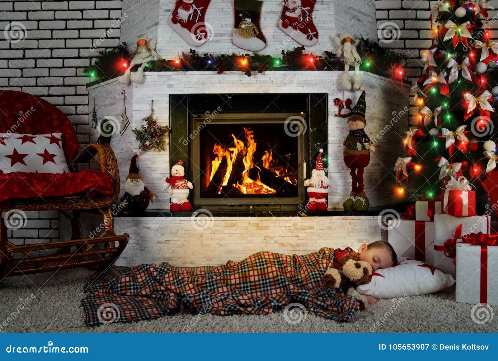 Un petit garçon dort avec un chien de jouet sous un arbre de Noël dans une chambre avec une cheminée brûlante