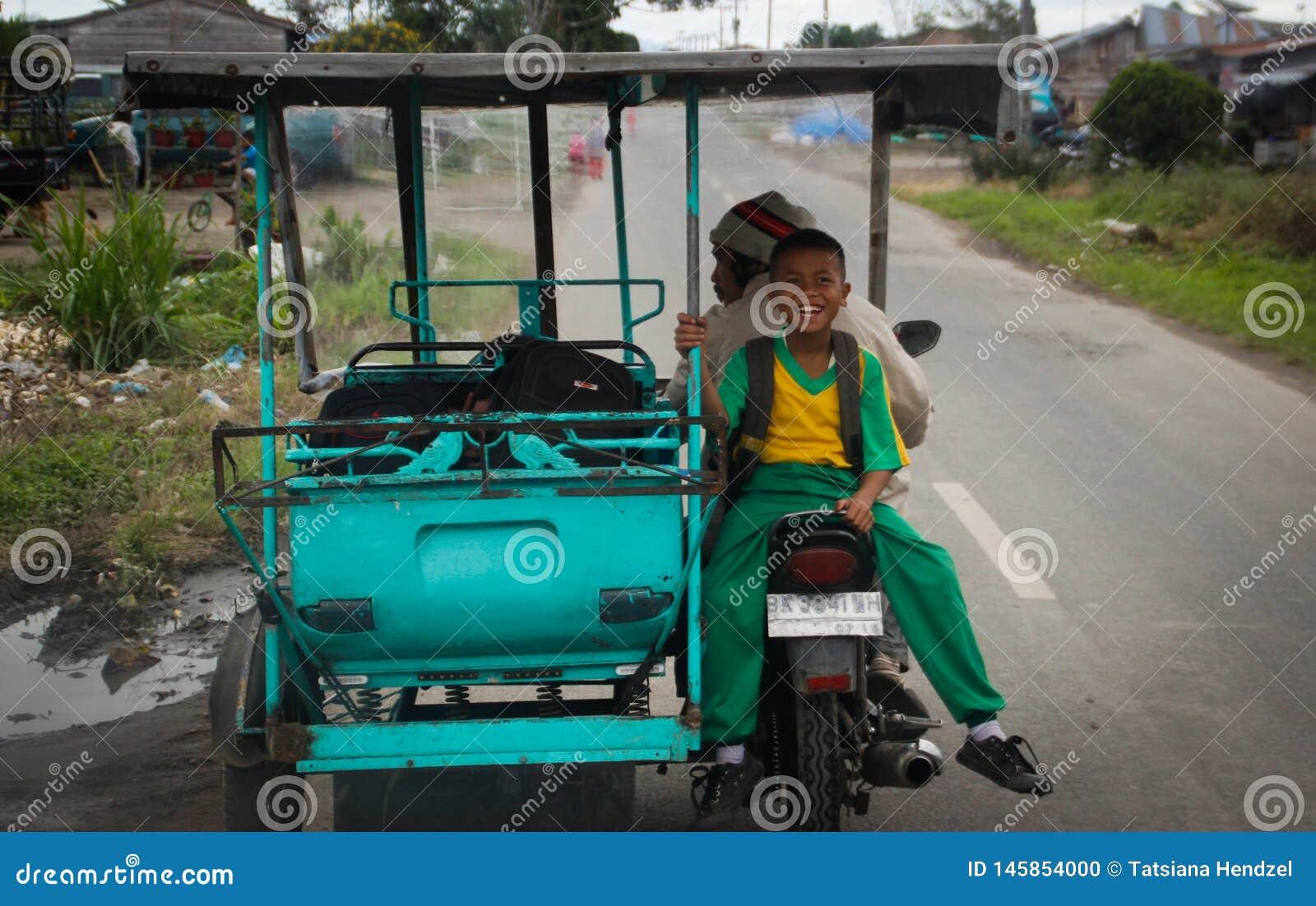 Un petit garçon indonésien monte un tuk-tuk et des rires joyeux