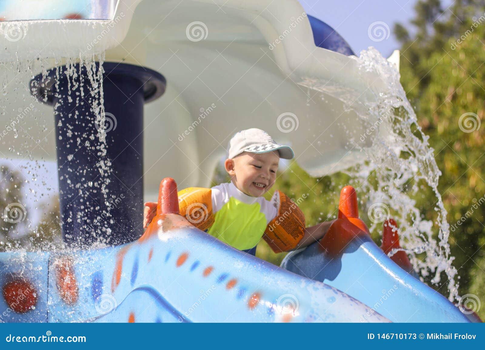 Un petit garçon roule vers le bas une glissière d eau La joie des enfants dans le parc aquatique Vacances d été pour des enfants