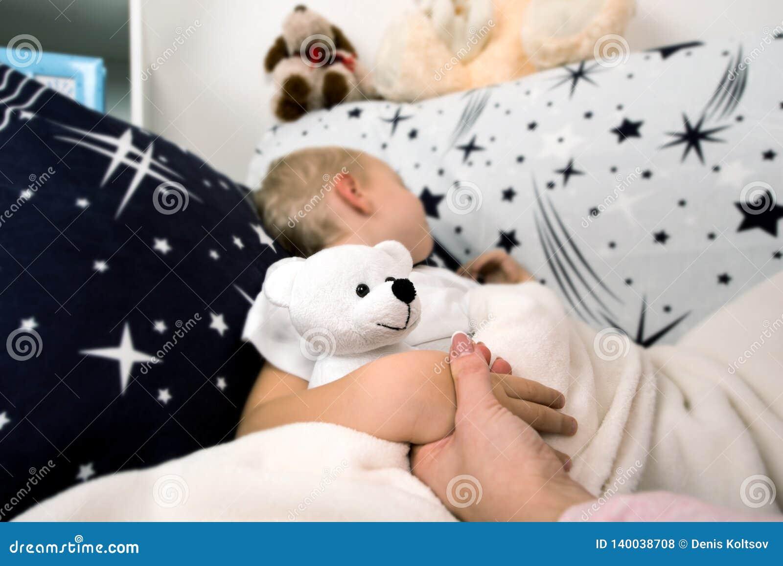 Un petit garçon se situe dans le lit La maman l embrasse doucement avant pour dormir