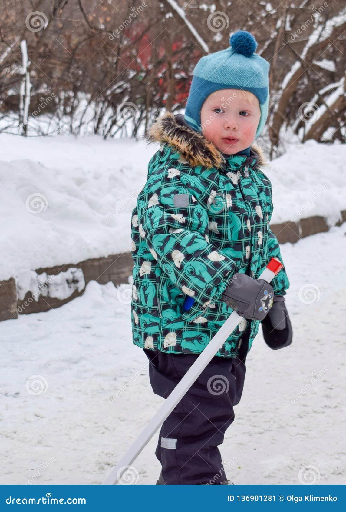 Un petit garçon se tient avec un bâton de hockey en hiver en parc neigeux
