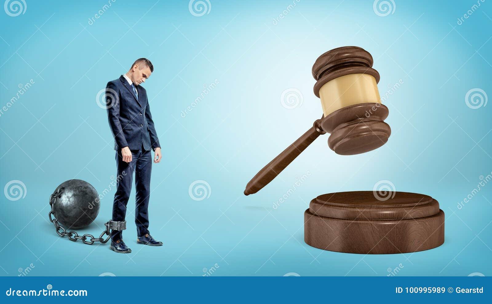 Un petit homme d affaires triste leashed aux supports d une boule de fer près d un marteau frappant géant de juge