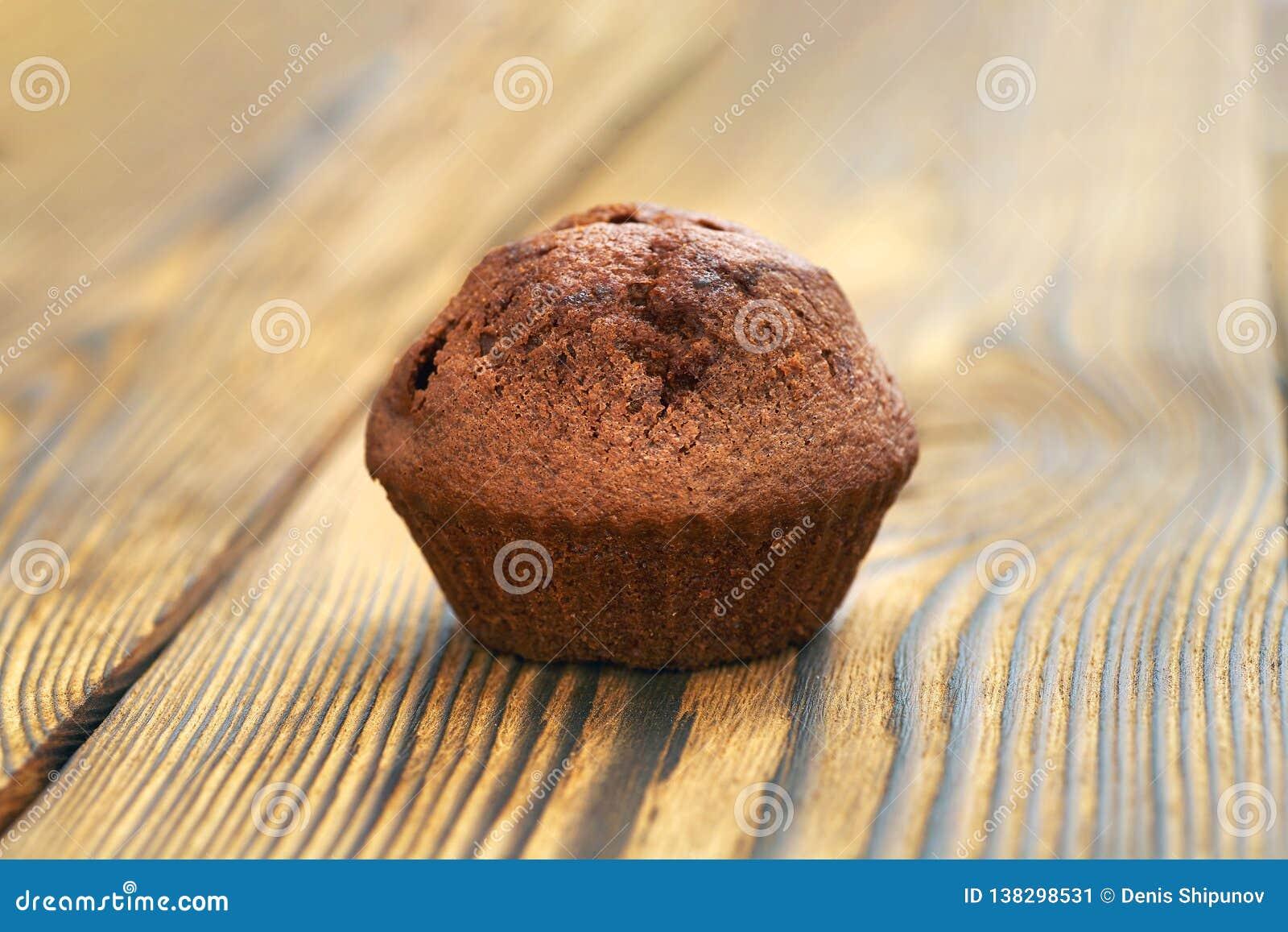 Un petit pain foncé de la pâte de chocolat sur le fond d une vieille table en bois
