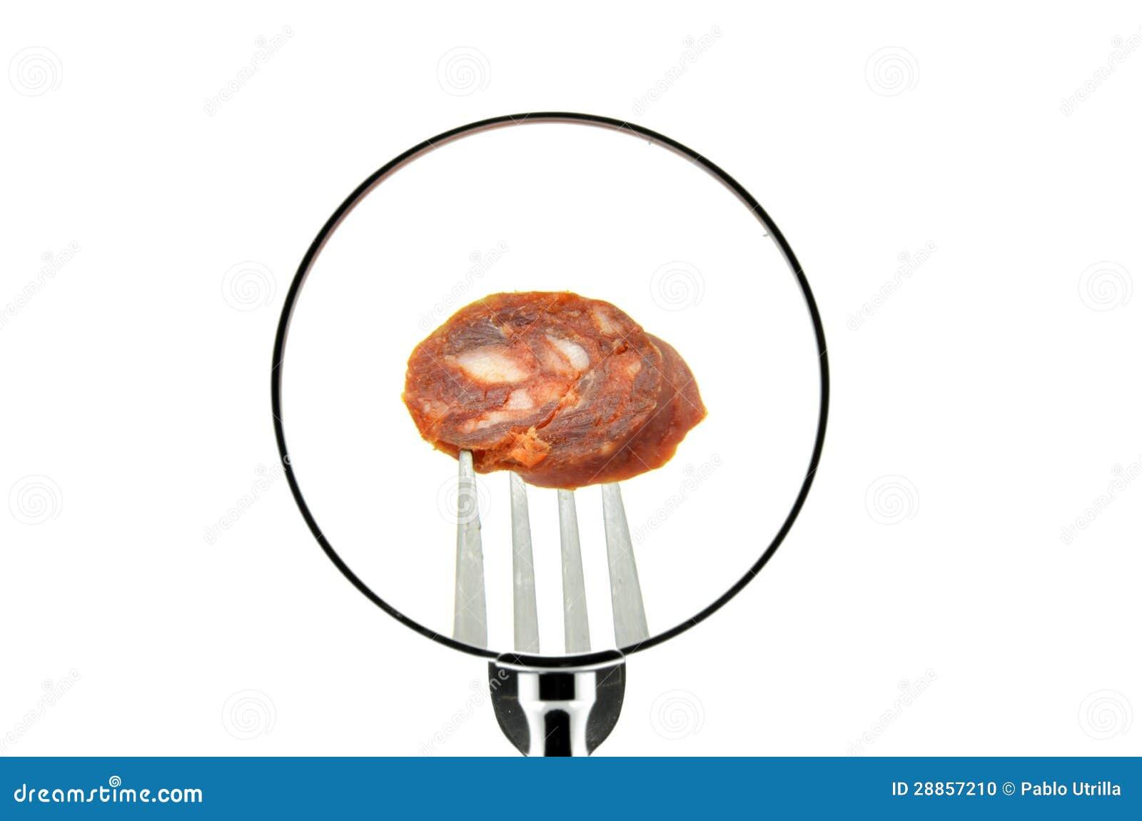 Un pezzo di salsiccia su una forcella ha perforato veduto dietro una lente d ingrandimento