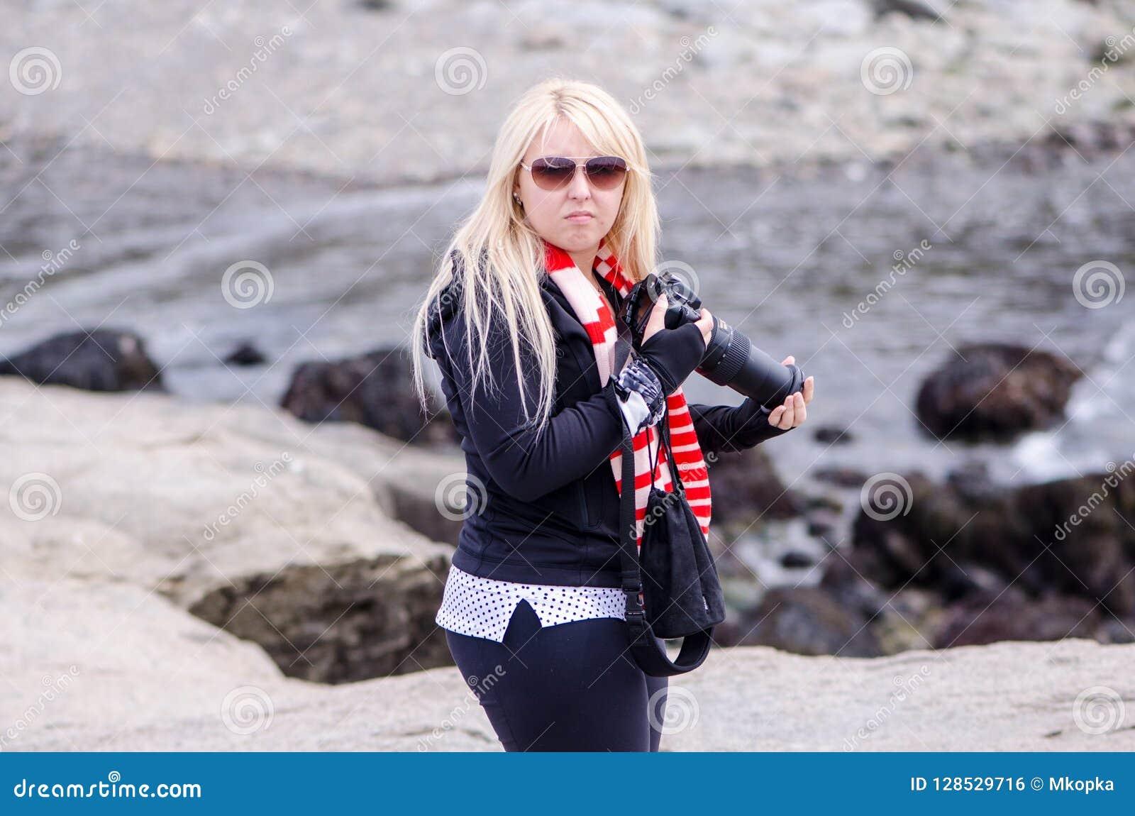 Un photographe féminin blond semble fâché et bouleversé
